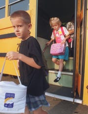 Aaron Frater, 7, and his sister Patti, 5, step off the bus at Pershing Elementary for their first day of the new school year.