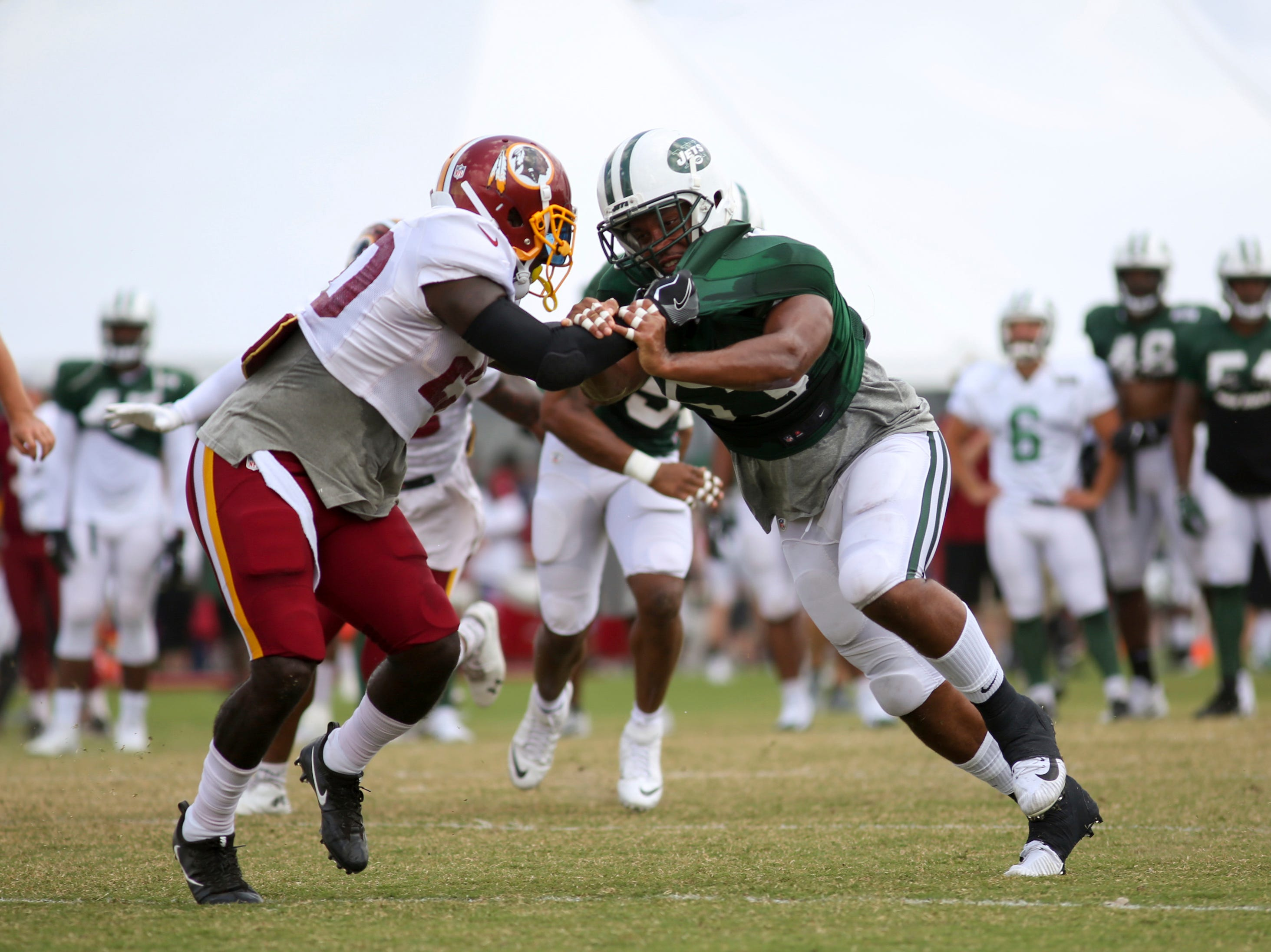 Washington Redskins running back Rob Kelley (20) blocks New York Jets linebacker Kevin Minter at their joint practice in Richmond on Sunday.