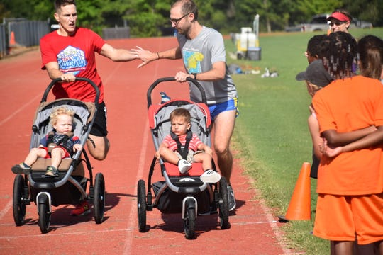 Relay handoff at the Gulf Winds Track Club Breakfast on the Track event.