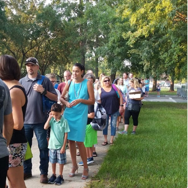Parents line up outside Killearn Lakes Elementary School waiting to walk their students to their classrooms on the first day of school.