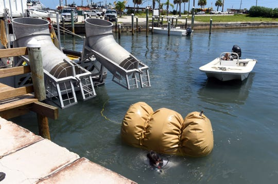 Levin Shavers, a member of the salvage crew with Maritime Research and Recovery, carefully removes the airbag used to float a cannon from the 1715 Spanish Plate Fleet before it is hoisted ashore on Monday, Aug. 13, 2018, at Fisherman's Wharf in Fort Pierce. The cannon, found off Sandy Point, will be treated and cleaned and put on display at Melody Lane Fishing Pier. The process will take about three years.