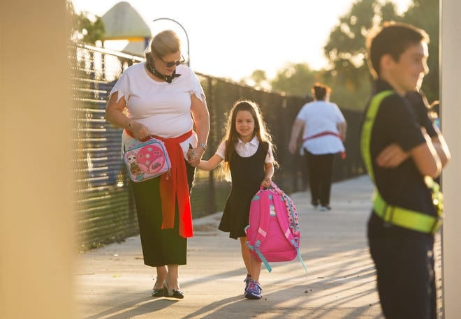 """Martin County school's superintendent Laurie Gaylord (left) walks kindergarten student Ava Ashenbaugh, 5, to her classroom as Gaylord visits Hobe Sound Elementary School students and faculty during their first day of school on Monday, August 13, 2018, in Hobe Sound. Gaylord dressed in support of the school's pirate theme for the day. """"We are really excited about all the new programs that we have to offer our students this year,"""" said Gaylord adding, """"It's exciting."""""""