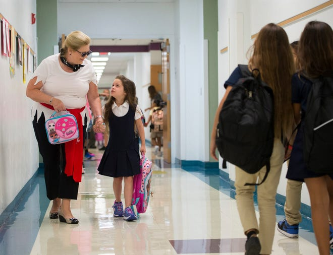 Martin County school's superintendent Laurie Gaylord (left) walks kindergarten student Ava Ashenbaugh, 5, to her classroom as Gaylord visits Hobe Sound Elementary School students and faculty during their first day of school on Monday, August 13, 2018, in Hobe Sound. Gaylord's tenure will expire in November 2020.