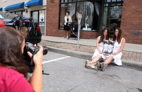 Carrie Yale photographs twin sisters Caitlin Kerrigan Karnbach, left, and Meghan Kerrigan Voccio, where she photographed them 33 years-ago during a fireman's parade on Main Street in Mount Kisco, Aug. 12, 2018. They were 3 years-old at the time.
