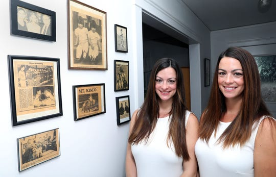 Twin sisters Caitlin Kerrigan Karnbach, left, and Meghan Kerrigan Voccio, beside a framed newspaper clipping of them from 33 years-ago taken during a fireman's parade in Mount Kisco, which still hangs at their parent's home in Mount Kisco Aug. 12, 2018. They were 3 years-old at the time.