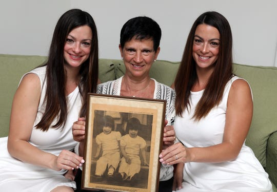 Twin sisters Caitlin Kerrigan Karnbach, left, and Meghan Kerrigan Voccio, and their mother Kathleen Kerrigan hold a framed 1985 newspaper clipping in Mount Kisco Aug. 12, 2018. The photo of the twins was taken 33 years-ago during a fireman's parade in Mount Kisco when they were 3 years-old.
