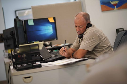 Duane Simpson, a service manager for Nickle Electric Companies in Newark, talks with a customer over the phone.