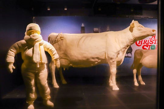 """This Monday, July 16, 2018, photo provided by the American Dairy Association Mideast shows Ohio State Fair butter sculptures including this year's sculptures marking the 35th anniversary of the 1983 movie """"A Christmas Story,"""" including the character Randy who """"can't put my arms down"""" due to his bulky snowsuit, left, and the display's customary cow and calf, right, in the Dairy Products Building at The Ohio Expo Center & State Fair in Columbus, Ohio. The American Dairy Association Mideast says sculptors spent more than 400 hours creating the refrigerated display unveiled Tuesday, July 24, 2018, crafted from more than a ton of butter."""