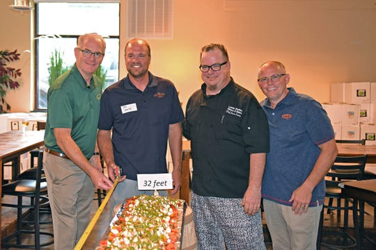 A 32-foot-long Caprese salad was made on Aug. 9,  by Chef Jason Dunn of Lewis Station Winery, Lake Mills, using Crave Brothers Farmstead Classics Fresh Mozzarella and local produce. Pictured are (from left) George Crave, President-Crave Brothers Farmstead Cheese,  Bill Marty, Owner -Earth Fresh Acres, Jason Dunn, Chef- Lewis Station Winery. Rob Lewis, Owner and Winemaker- Lewis Station Winery