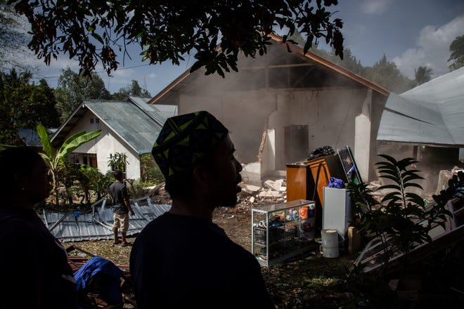 Villagers pull down their damaged house  in Kayangan on August 12, 2018 in Lombok Island, Indonesia.