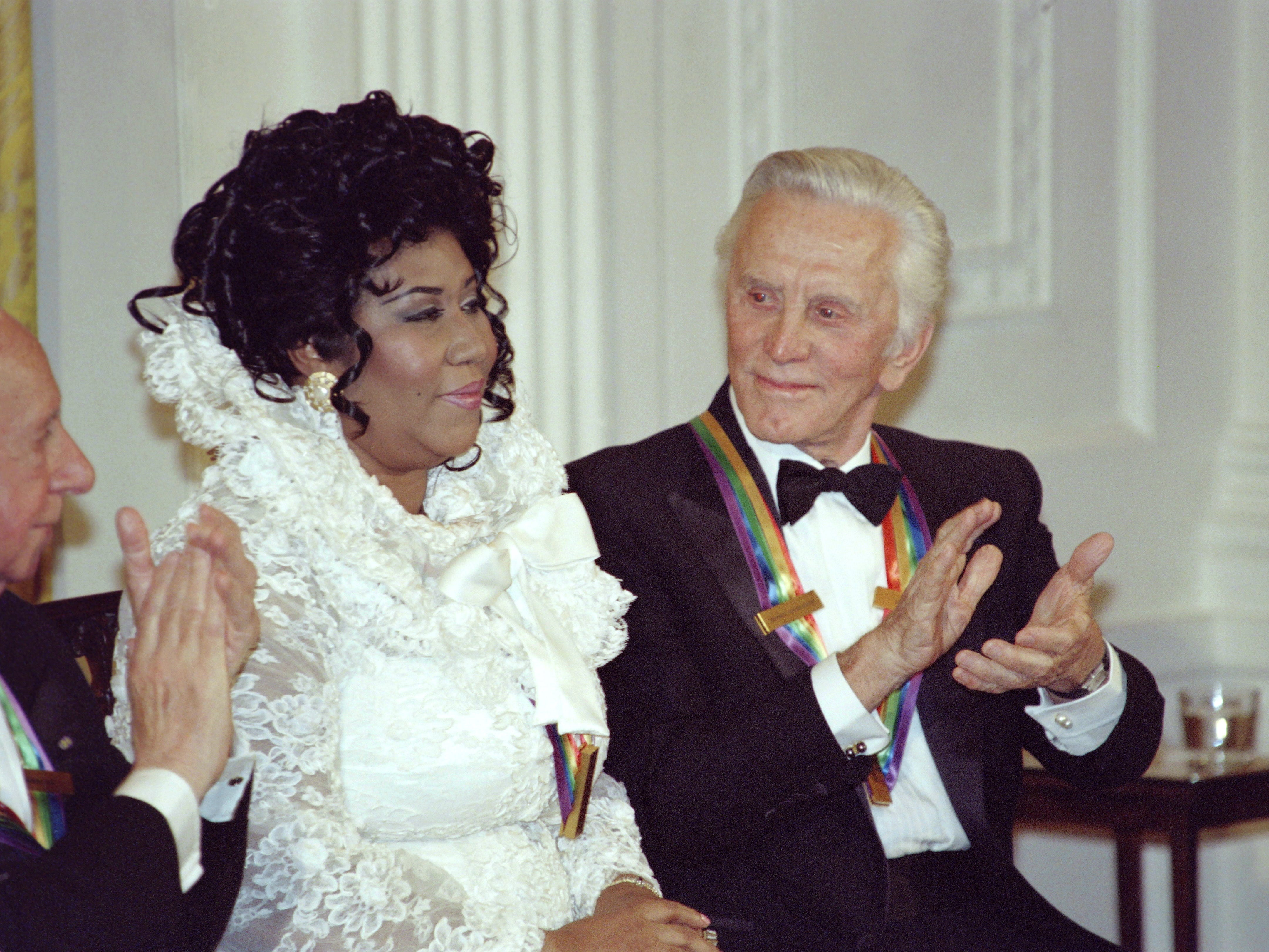 US actor Kirk Douglas (R) applauds singer Aretha Franklin at a reception for the Kennedy Center Honors on December 04, 1994 at the White House in Washington DC. The Kennedy Center Honors recognizes American performance artists who have made lifetime contributions to American culture. Person at left is unidentified. AFP PHOTO JOSHUA ROBERTS (Photo credit should read JOSHUA ROBERTS/AFP/Getty Images)
