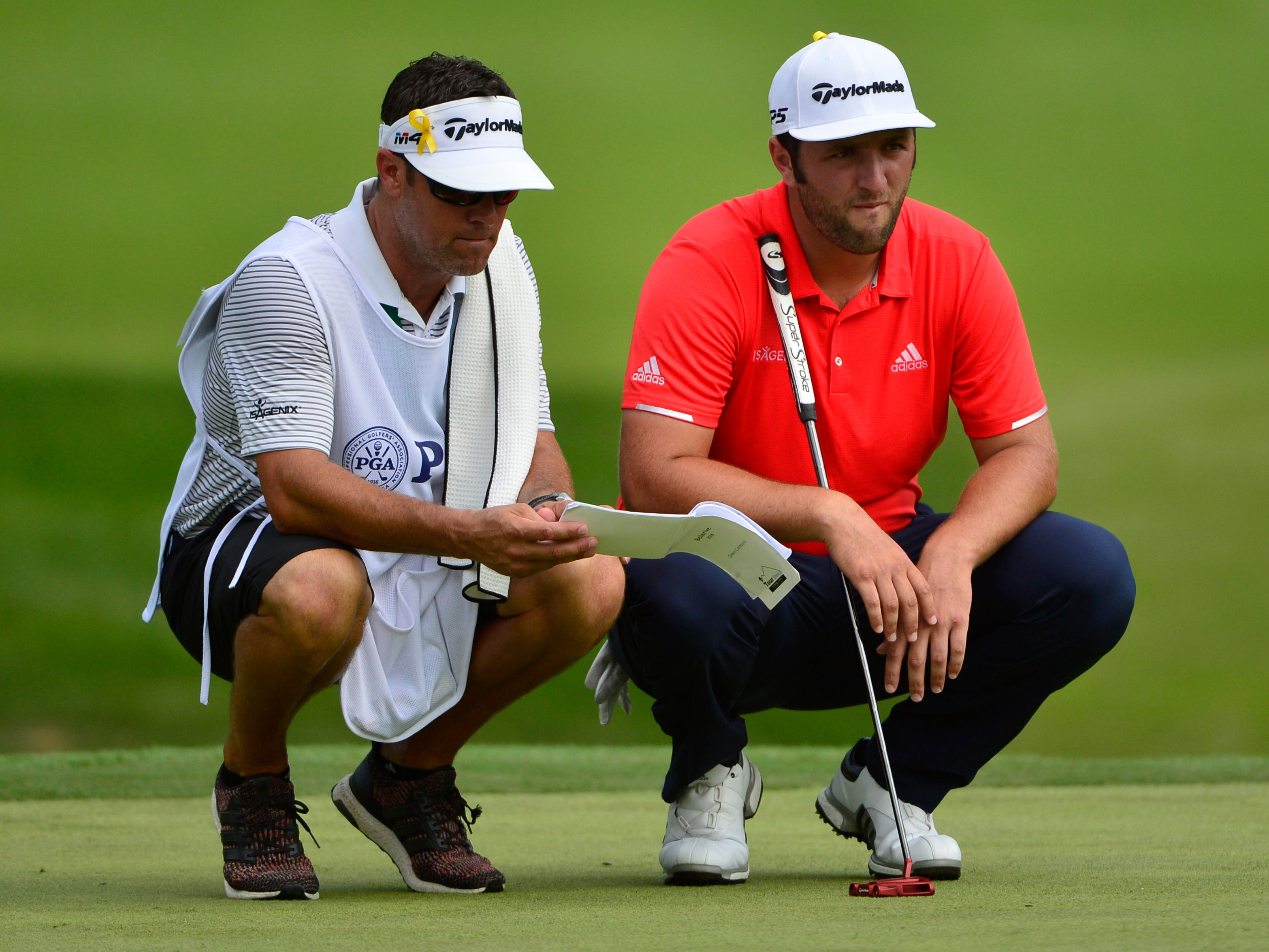 Jon Rahm consults with caddie Adam Hayes on the 10th green.