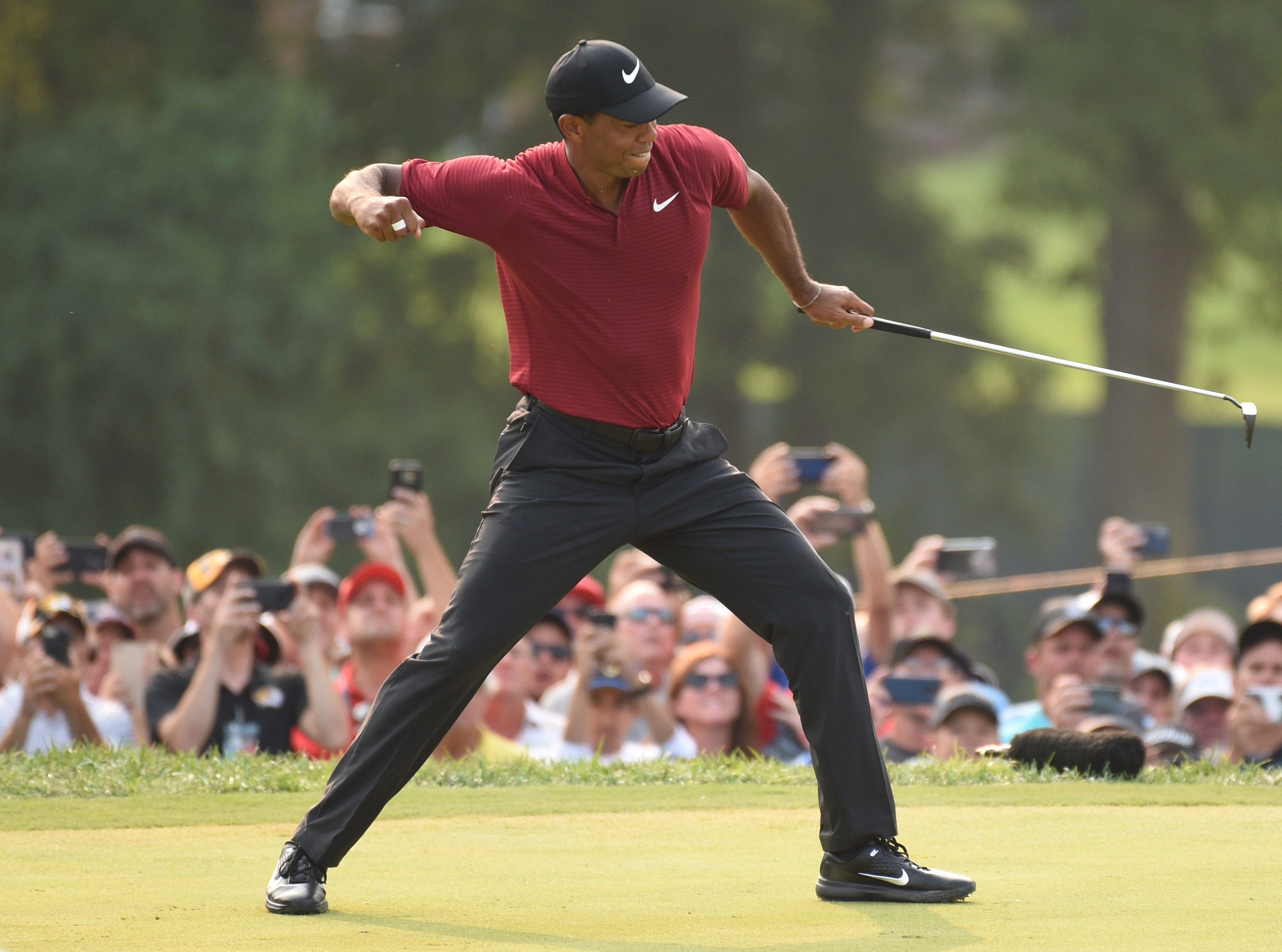 Tiger Woods celebrates after making a birdie putt on the 18th green.