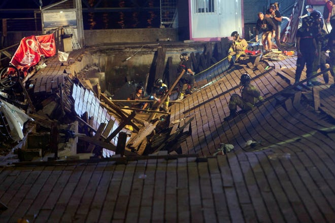 Several firefighters search for victims after several dozen people fell into the sea when a wooden gateway collapsed during a concert in Vigo, northwestern Spain, late on 12 August 2018.