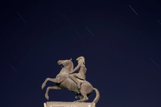Perseid meteors cross the sky over the statue of Alexander the Great at the Church of Deir Hajla near the West Bank city of Jericho, late Sunday, Aug. 12, 2018.