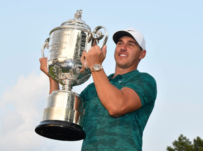 Brooks Koepka holds up the Wanamaker Trophy after winning the PGA Championship at Bellerive Country Club.