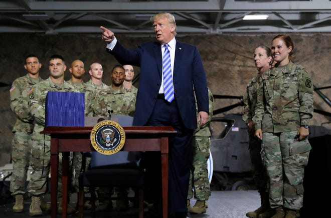 President Donald Trump points to the crowd as he signs the $716 billion defense policy bill named for Sen. John McCain during a ceremony Monday, Aug. 13, 2018, in Fort Drum, N.Y.