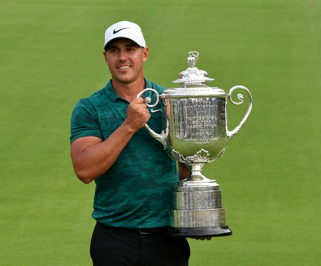 Brooks Koepka celebrates with the Wanamaker Trophy.