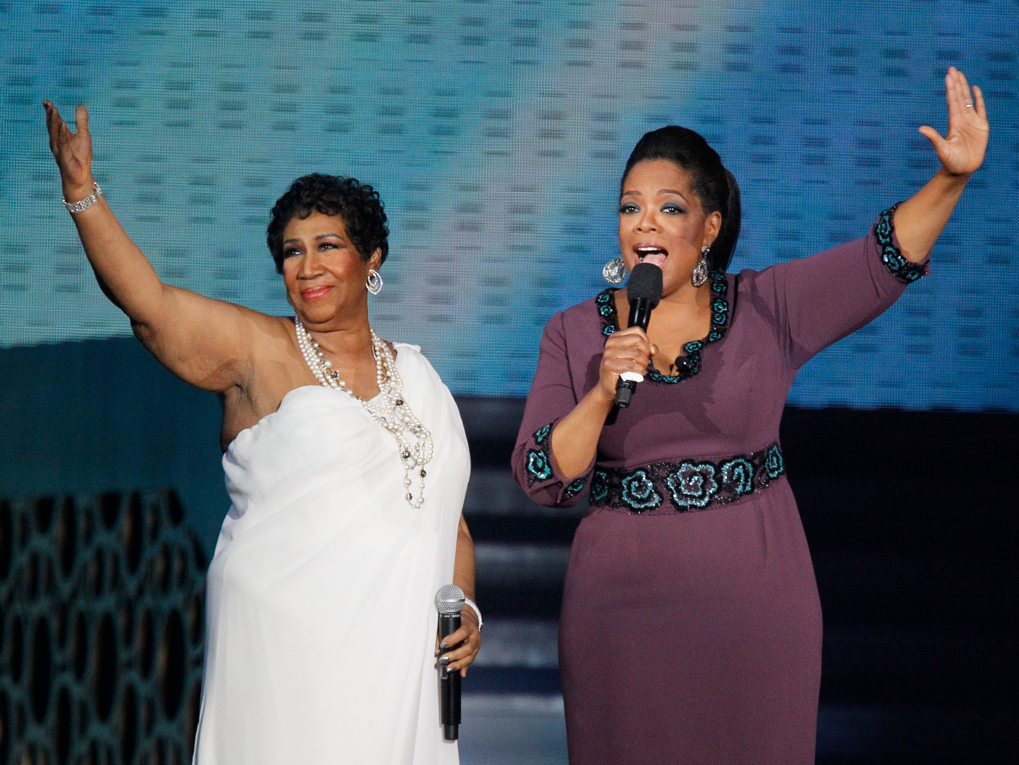 "Aretha Franklin and Oprah Winfrey acknowledge fans during a star-studded double-taping of ""Surprise Oprah! A Farewell Spectacular,"" Tuesday, May 17, 2011, in Chicago. ""The Oprah Winfrey Show"" is ending its run May 25, after 25 years, and millions of her fans around the globe are waiting to see how she will close out a show that spawned a media empire. (AP Photo/Charles Rex Arbogast)"