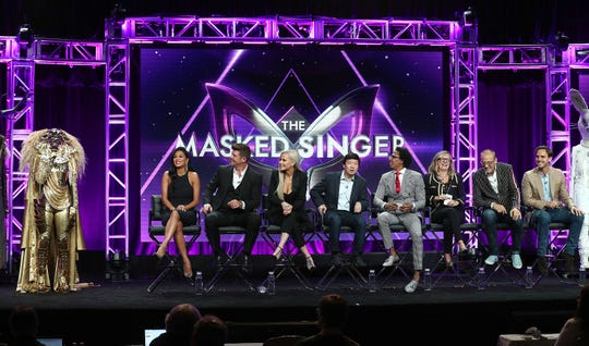 """An unidentified celebrity in an elaborate lion costume is one of the competitors on Fox's """"The Masked Singer"""" reality series, seen with judges Nicole Scherzinger, Robin Thicke, Jenny McCarthy and Ken Jeong, and host Nick Cannon at a press event."""