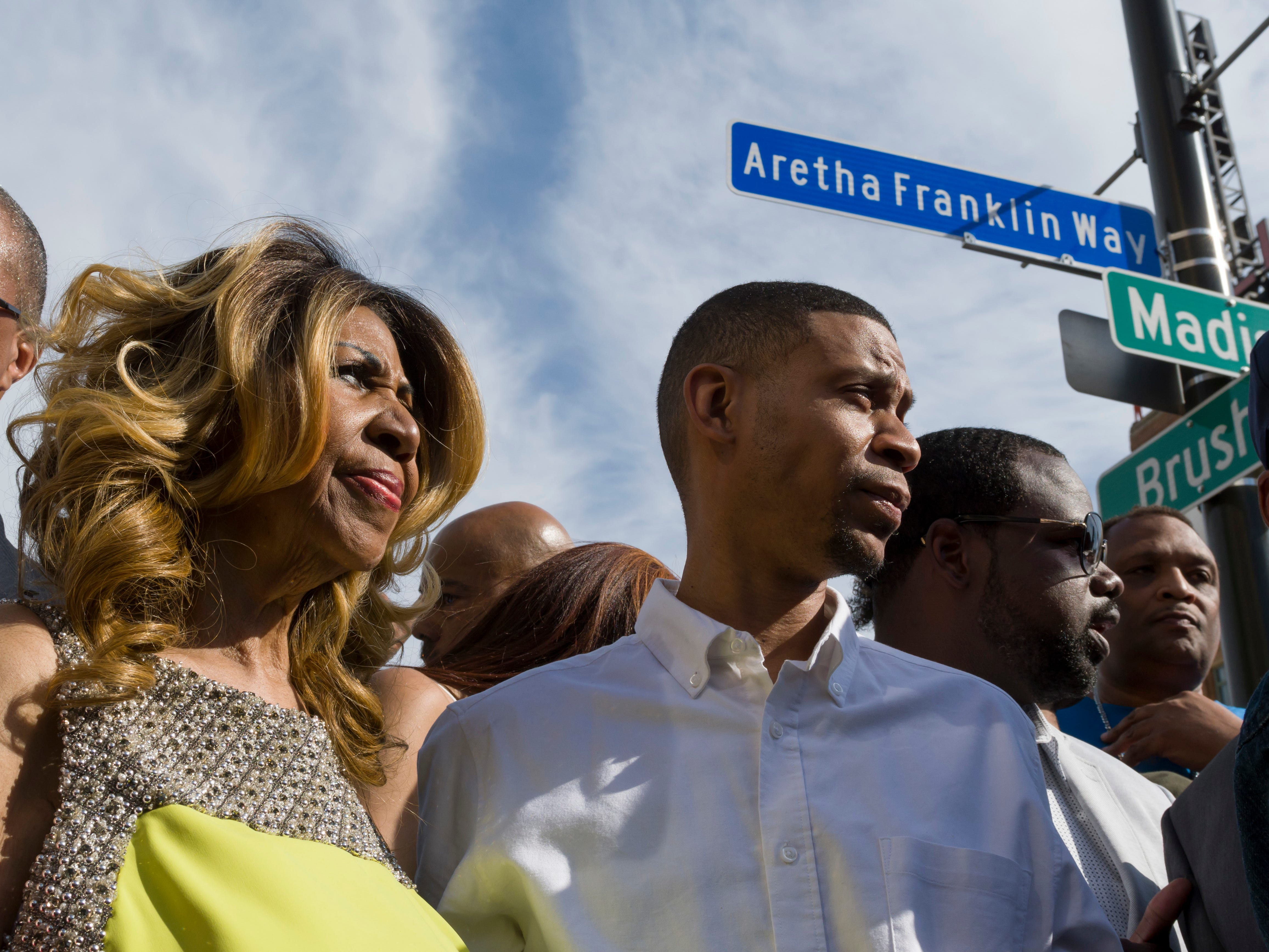 Aretha Franklin and her son Kecalf Cunningham stand under the newly unveiled street sign in front of the Music Hall in Detroit, June 8, 2017. (David Guralnick/Detroit News via AP) ORG XMIT: MIDTN102