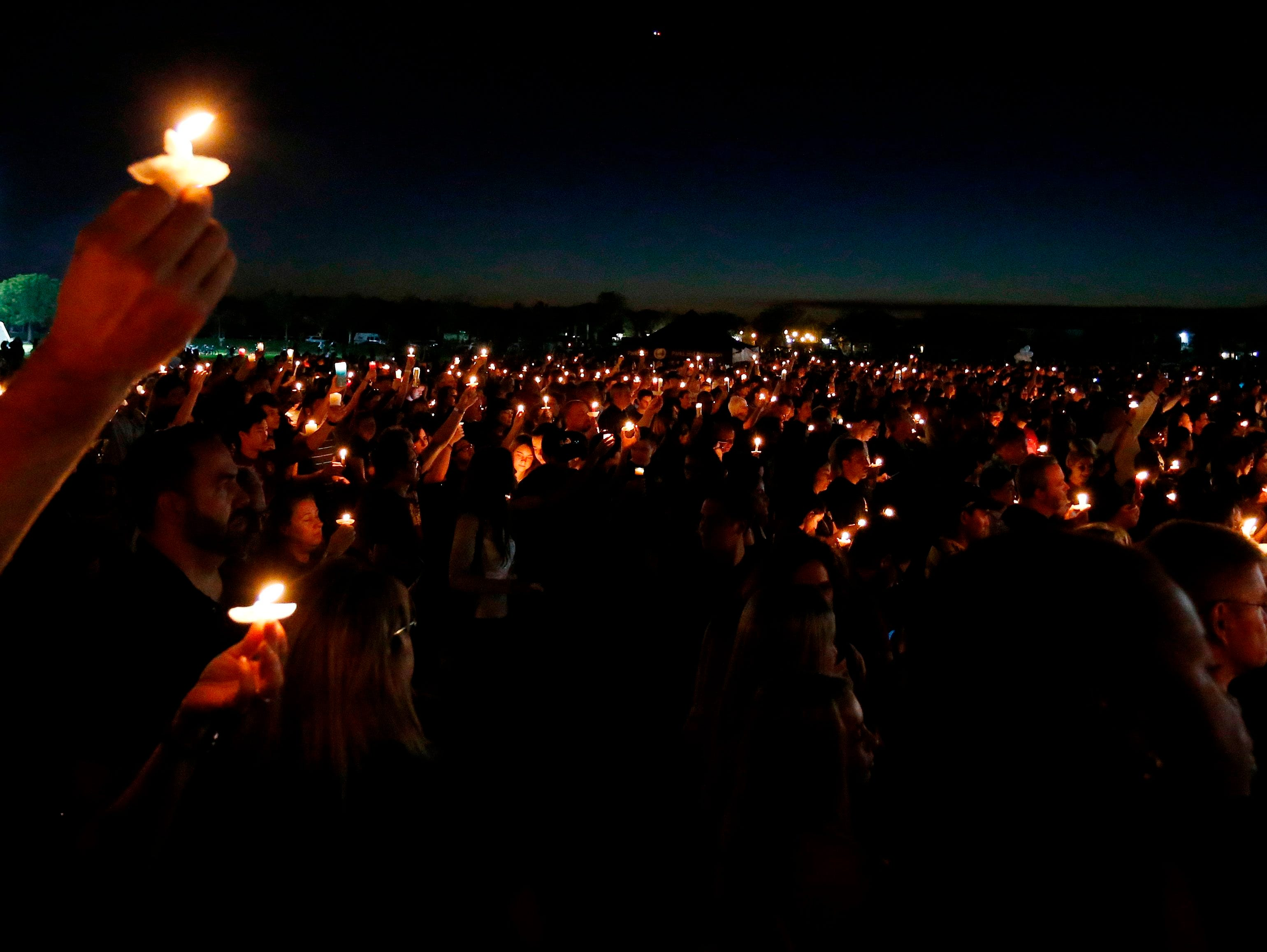 Thousands of mourners hold candles during a candlelight vigil for the victims of Marjory Stoneman Douglas High School shooting in Parkland, Florida on February 15, 2018.