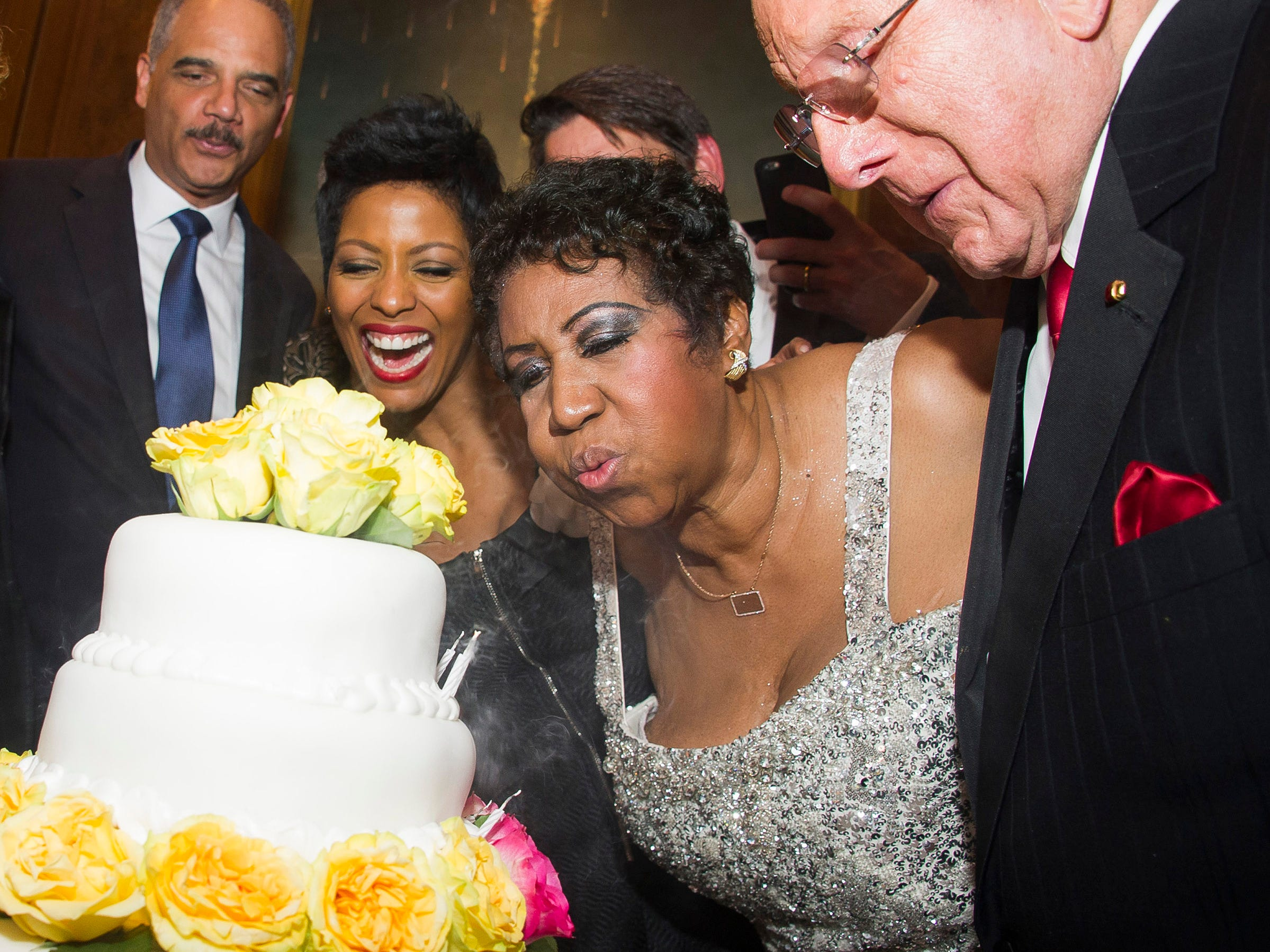 Aretha Franklin blows out the candles on her birthday cake accompanied by, from left to right, Attorney General Eric Holder, Tamron Hall and Clive Davis during Aretha's annual birthday bash at The Ritz Carlton on Sunday, March 22, 2015, in New York. (Photo by Charles Sykes/Invision/AP) ORG XMIT: NYCS108