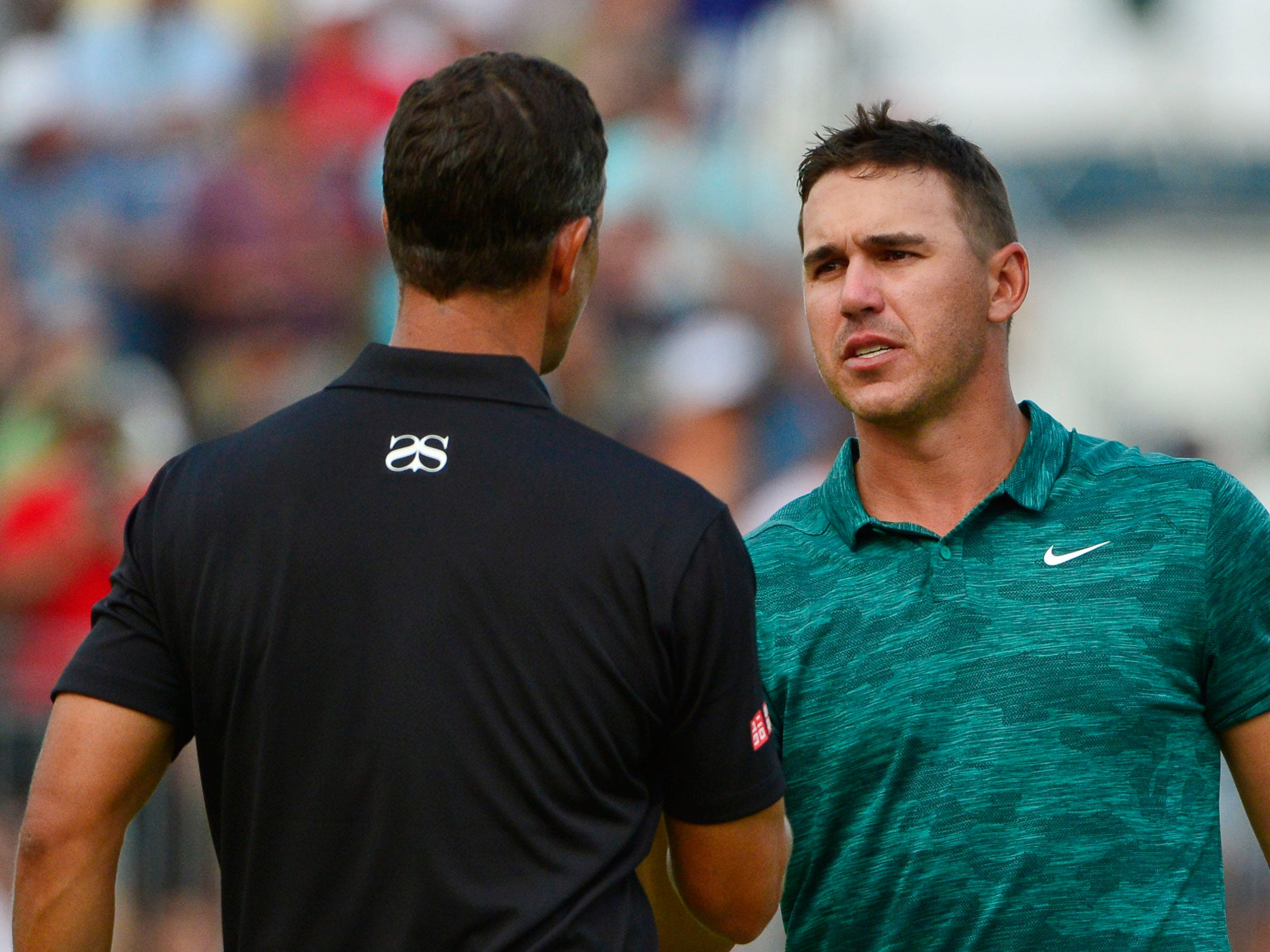 Brooks Koepka (right) shakes hands with Adam Scott on the 18th green.