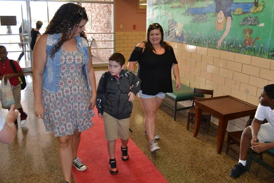 Carson Redmon (center), a third grader, walks the red carpet Tuesday as he returns to school at Cherokee Elementary. Joining him are Pre-K teacher Charlie McCall (left) and his mother Carla Elliott (right).