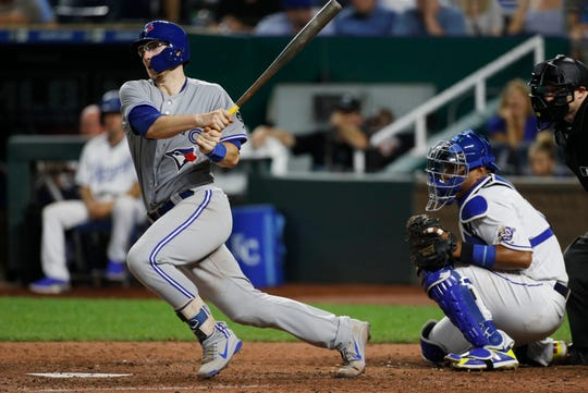 Toronto's Danny Jansen, left, singles to left field in his first major league at-bat against the Kansas City Royals on Monday night.