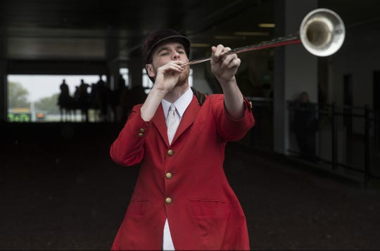 Bugler Joseph Luckenbill blows his horn for post time as the 2017 season gets underway at Monmouth Park in Oceanport.