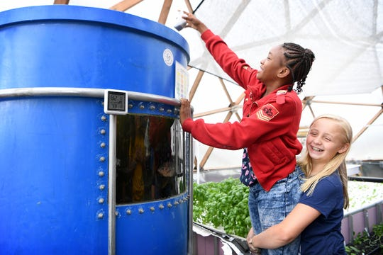 Jameriyah Collins, 11, gets a little help from Kyndal Devlin, 10, so she can feed the fish in the Eliada Farms' geodesic grow dome on Thursday, Aug. 9, 2018. Filtered waste from the tilapia is used in aquaponics to grown plants in the dome and the fish will one day be eaten as well.