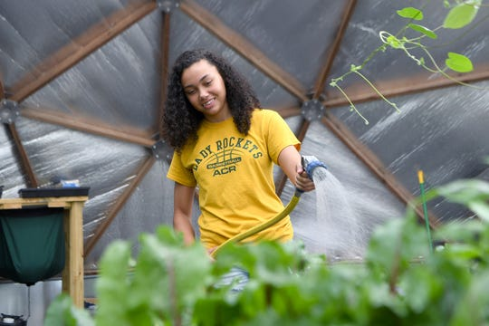 The Jaden Jones waters plants inside of Eliada Farms' geodesic grow dome on Thursday, Aug. 9, 2018. The plants growing in the dome are meant to be nutritional, educational and therapeutic.