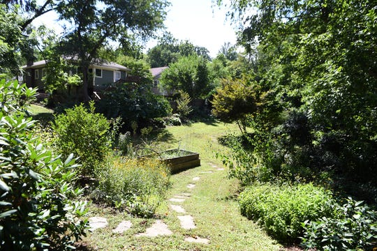 """The backyard of Ginger Graziano's home in West Asheville opens up to a long grassy lot with trees, flowers and other plants creating a lush perimeter. Graziano has been creating the garden for 17 years and each year comes out """"with a pick axe and does more"""" she said."""