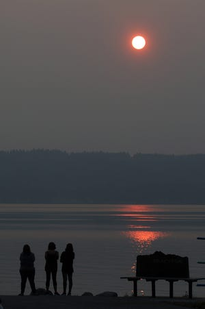 The sun sets Monday through a smoky haze as seen from the Tracyton boat ramp. Changing weather conditions are expected to clear out some of the smoke by Wednesday.