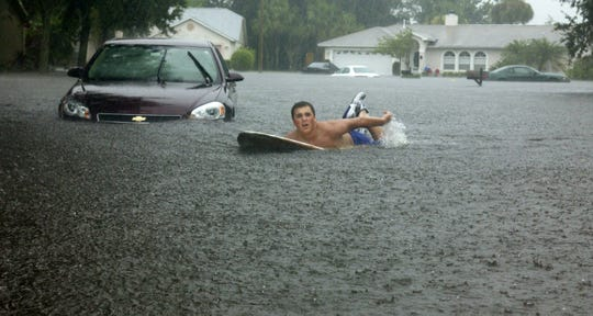 Surf's up, as several young people made the best of a bad situation on Aug. 20, 2008. Parkway Meadows subdivision in north Melbourne had major flooding.