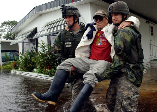 Ross Roberton, a 14-year resident of Lamplighter Village is helped to a transport vehicle by Sgt. Justin Davenport, left, and SPC George Smith, both of the National Guard out of Cocoa, on Aug. 21, 2008.