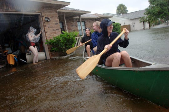 Ramona Bernard, left, prepares to leave her home as Laura Coffey, Nicole Morahan and Brenda Morahan help carry her belongings across the street in a canoe on Empire Ave. in Melbourne on Aug. 20, 2008.