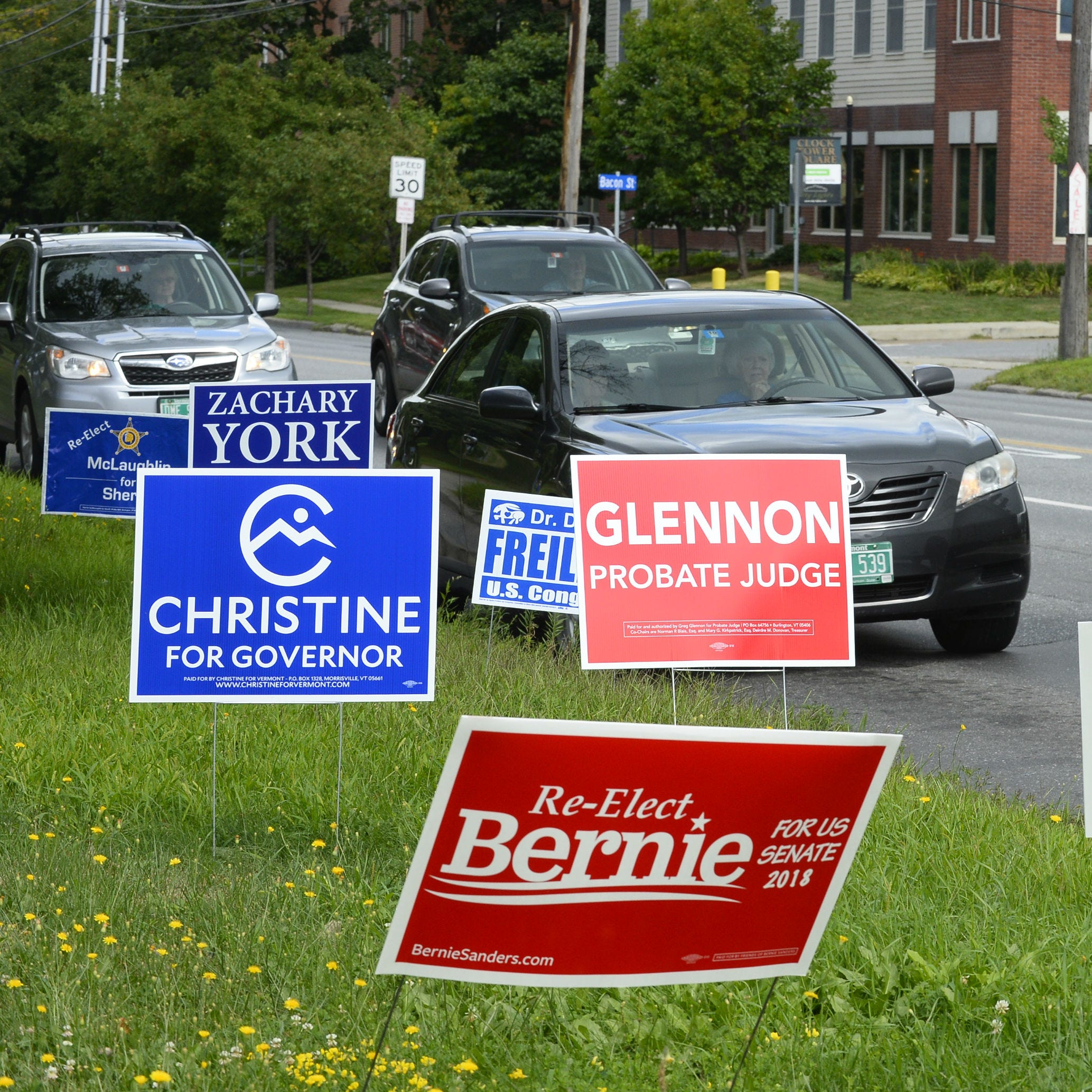 Traffic flows by campaign signs planted alongside Shelburne Road in Burlington on Tuesday, August 14, 2018.