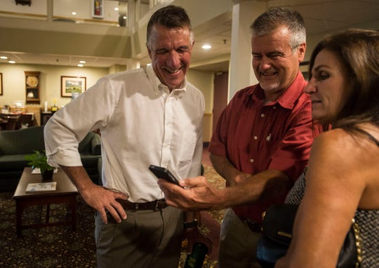 From left, Gov. Phil Scott, Steve Larrabee -- father of Scott's Campaign Manager Brittney Wilson -- and wife Diana McTeague Scott chuckle over anecdotes on the campaign trail at the Comfort Inn & Suites in Berlin just after polls closed on Tuesday night, Aug. 14, 2018, where a small group of friends and members of Scott's administration gathered to await primary election results.