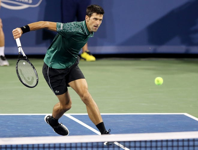Novak Djokovic runs to return a hit from Steve Johnson during the Western and Southern Open on Center Court at the Lindner Family Tennis Center in Mason Monday, August 13, 2018.