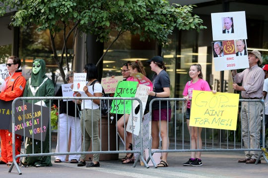 About 20 demonstrators gathered outside the Westin Hotel ahead of Vice President Mike Pence's visit, Tuesday, Aug. 14, 2018, in Cincinnati.