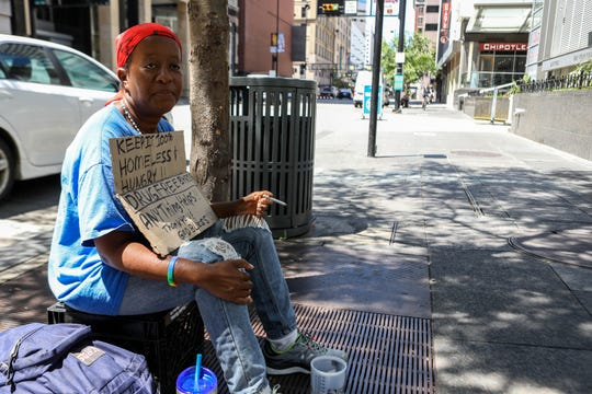 A homeless woman named Amber sits outside at Fountain Square.