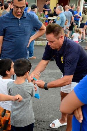 "Police Chief Richard Trigo hands out ""Bless The Blue"" wristbands."