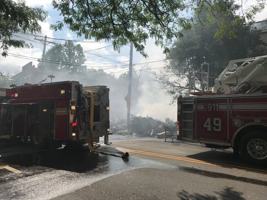Firefighters continue to douse rumble left when a truck crashed into a building in Frenchtown Monday night, starting a fire that destroyed and damaged several buildings.