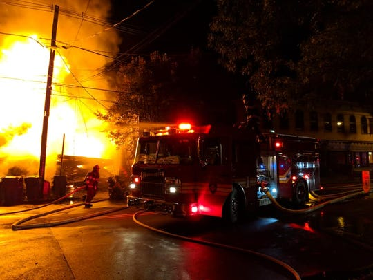Firefighters battle a massive blaze in Frenchtown Monday night which started after a truck crashed into a business.