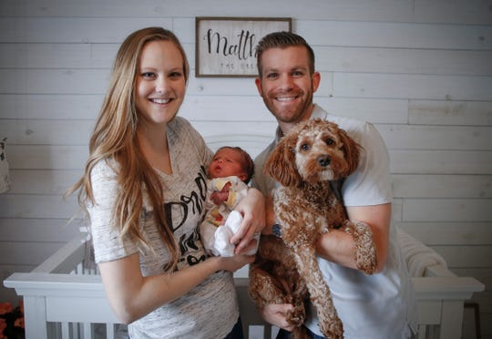 Drew and Ariann Corpstein hold their son, Matthew, and dog, Lola, at their home in Ankeny on Tuesday, August 14.