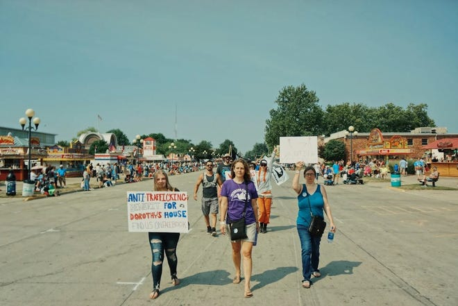 Chloe Craig (left), 15, marches with her mother Misti Craig (right), organizer Melissa Fuller (middle) and Veterans For Peace to advertise a fundraiser for Dorothy's House at the Iowa State Fair on Monday, August 13.