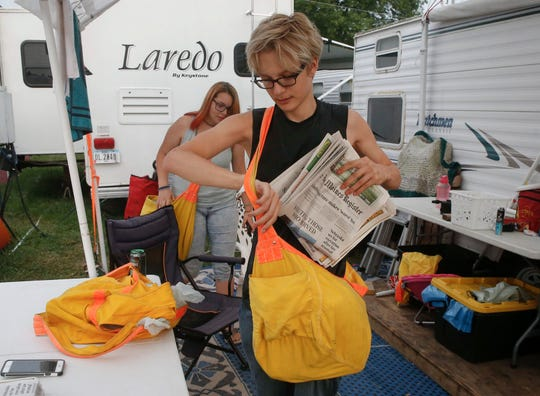 Dredun Gunn, 16, of Des Moines, fills his newspaper bag with copies of the Des Moines Register to sell to campers at the Iowa State Fair campgrounds on Tuesday, Aug. 14, 2018, in Des Moines.