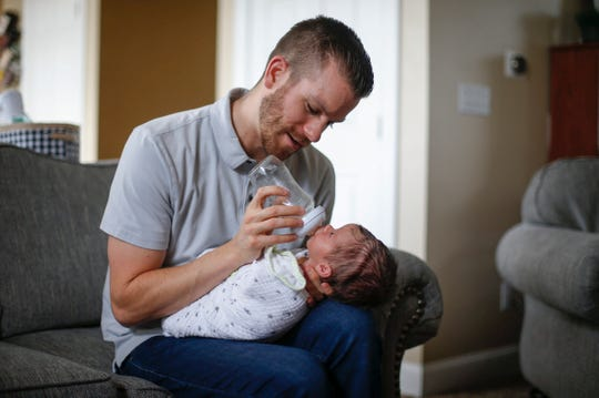 Ten-day-old Matthew Corpstein looks up at his father, Drew, as he drinks a bottle on Tuesday, Aug. 14, 2018, in Ankeny.